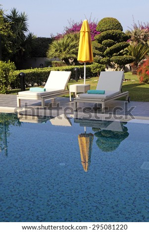 Vertical view with white outdoor furniture and yellow umbrella near the swimming pool for relax on summer resort. Selective focus