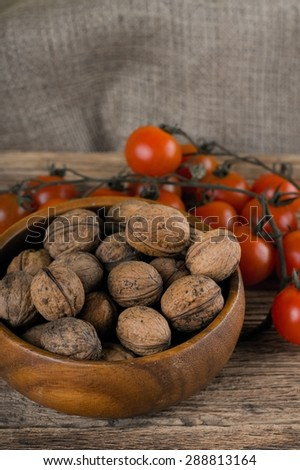Vertical vintage photo of wooden bowl full of walnuts and branch of cherry tomatoes placed on wood table with jute cloth around a desk. - stock photo
