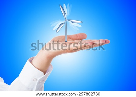 Vertical wind turbine turning its rotor blades while firmly moored in the open palm of a horizontal hand. Close up over sky blue background with bright gradient center. Wind energy business concept. - stock photo
