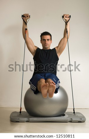 Vertically framed shot shot of a young athletic man doing Pilates on a balance ball. Isolated against a gray studio background - stock photo