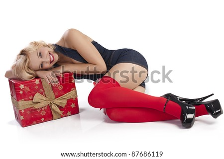 very attractive and sexy blond pin up with red christmas stocking and a big present box laying on the floor
