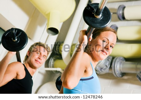 Very attractive and sportive couple doing power gymnastics with barbells