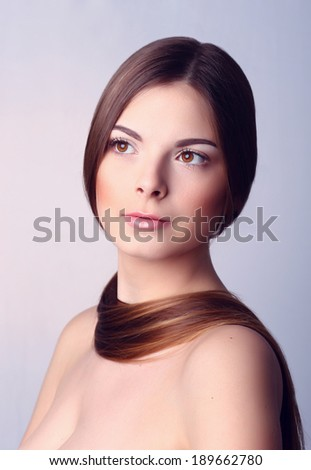 very attractive young brunette with long hair   and has a lock of hair around her neck. - stock photo
