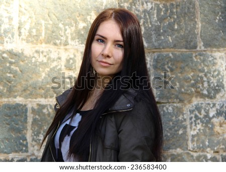 very beautiful and cute girl standing in front of a brick wall - stock photo