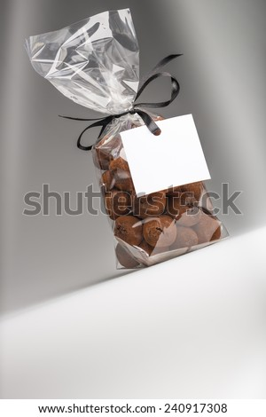 Very beautiful and delicious gift of chocolate truffles. Blank label that you can add your own trademark or your own message. Fun composition and lighting. Shooting in studio. - stock photo