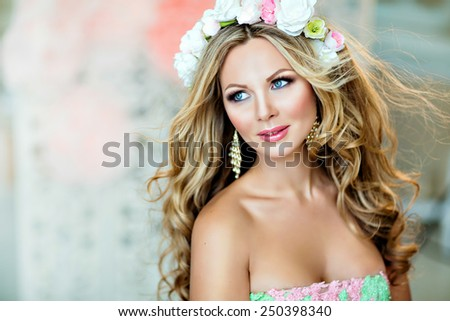 Very beautiful and sensual blonde girl with a wreath of delicate spring flowers, close up - stock photo