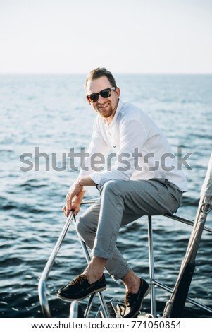 Very beautiful and stylish portrait of a charming guy with glasses and with beard, with a very nice smile, on the sea background
