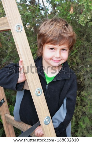 Very beautiful blond boy climbed a wooden extension ladders in the garden