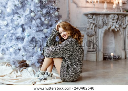 Very beautiful blonde girl in a knitted sweater and socks sitting and smiling against a white Christmas tree and fireplace - stock photo