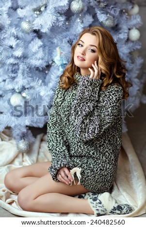 Very beautiful blonde girl in a knitted sweater and socks sitting on the background of the Christmas tree - stock photo