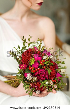 Very beautiful bouquet in red tones, which holds the girl in white dress