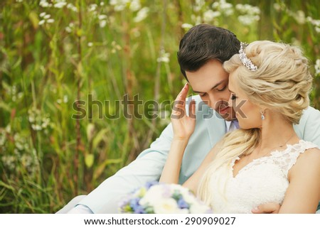 Very beautiful bride and groom embracing in a field where many colors and beautiful nature