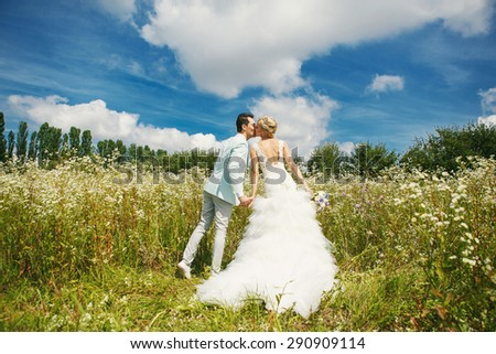 Very beautiful bride and groom kissing in a field where many colors and beautiful nature