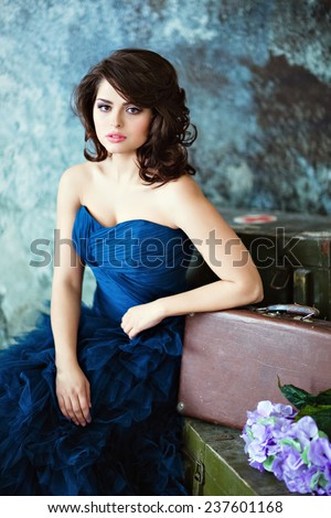 Very beautiful brunette girl in a blue dress sitting near suitcases against the wall - stock photo