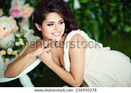 Very beautiful girl brunette in a beige dress laughs and looks away - stock photo
