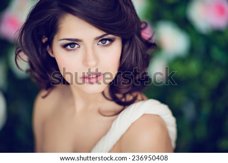 Very beautiful girl brunette in a beige dress looks straight, close up - stock photo