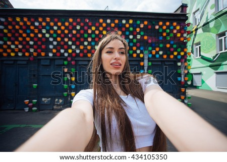 Very beautiful girl student doing selfie for instagram on vacation in Europe.Shooting outdoors.Beautiful bright background.Pretty girl photographed themselves outdoors.