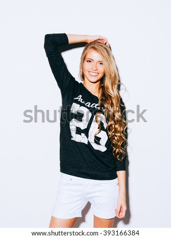 Very beautiful girl with long blond hair posing on a white background. She raised her hand above her head and smiling. Sweatshirt and white shorts. Indoor. Warm color. Hipster. - stock photo