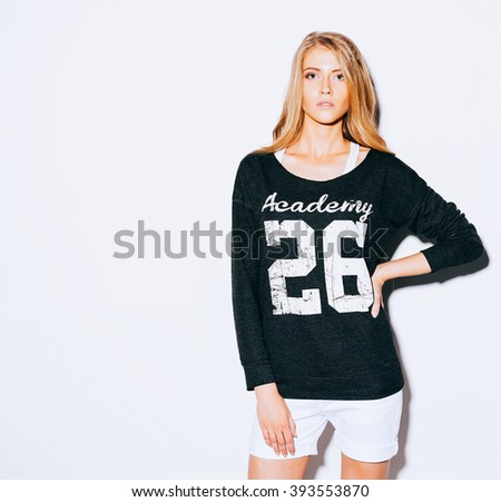 Very beautiful girl with long blond hair posing on a white background. Sweatshirt and white shorts. Indoor. Warm color. - stock photo