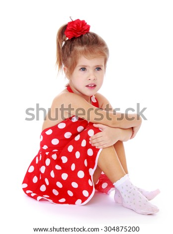very beautiful little girl with a red bow on her head. The girl dressed in red, summer, short polka dot dress. Girl sitting on the floor in white socks hugging her legs turned sideways to the camera - stock photo