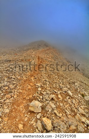 very beautiful mountain trail in fog - stock photo