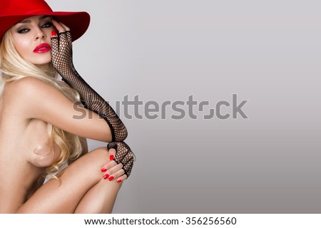 Very beautiful naked young blond sexy female model in erotic lingerie , black gloves in a cute makeup and sensory mouth, red lips on a black background with hearts and red hut, carnival look - stock photo