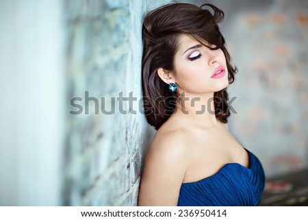 Very beautiful sexy brunette girl in a blue dress standing against the wall with his eyes closed - stock photo