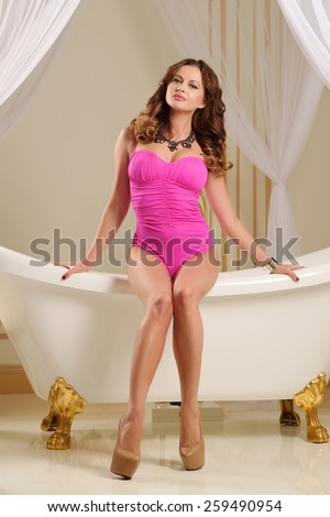 Very beautiful sexy young girl in a pink bathing suit with big breasts, full lips, jewelry, slim, athletic build,� , brunette, in the interior of a bathroom in beige and golden tones - stock photo