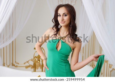 Very beautiful sexy young girl in green dress with big breasts, full lips, slim, athletic build,� , brunette, in the interior of a bathroom in white and golden tones - stock photo