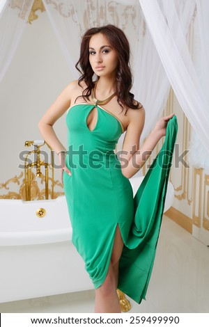 Very beautiful sexy young girl in green dress with big breasts, full lips, slim, athletic build, brunette, in the interior of a bathroom in white and golden tones - stock photo