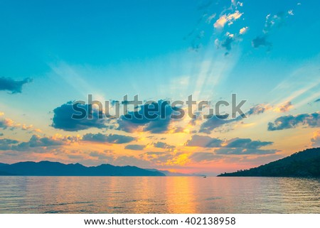 very beautiful sky in the rays of the rising sun over the sea - stock photo