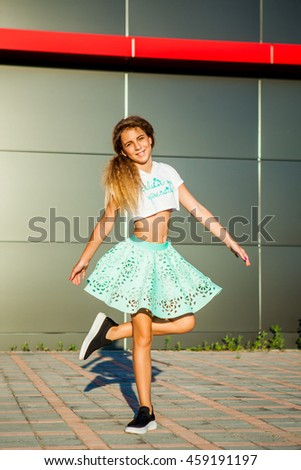 Very beautiful slim tanned young girl in a short blue skirt and a short white top and black shoes spinning and laughing in front of the shopping center building. Summer. Ukraine.