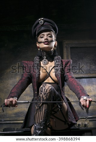 Very beautiful woman in a cap, with a whip - stock photo