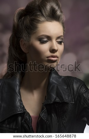very beautiful young brunette female posing in dark fashion shoot with creative hair-style and modern leather jacket  - stock photo