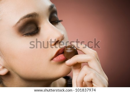 Very beautiful young brunette woman tasting fine chocolate. - stock photo