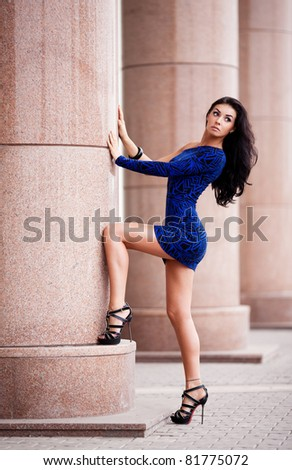 very beautiful young brunette woman wearing a mini dress in the street