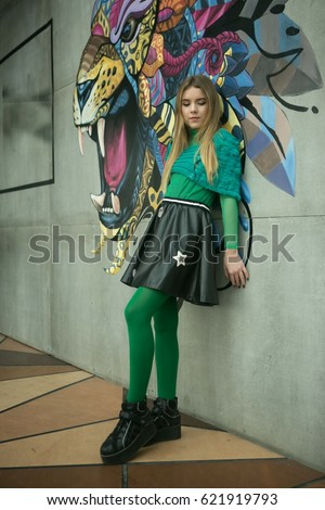 Very beautiful young girl blonde teen with beautiful legs in green tights and a green skirt in leather skirt.
