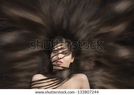 very beautiful young lady with long laying hair around her and some on face and body - stock photo