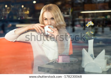 Very beautiful young woman, sit in  Cafe and drink coffee or tea with croissant, street front window view  - stock photo