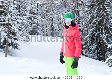 Very beautiful young woman wearing red jacket and green pants skiing in the Alps - stock photo