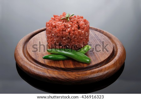 very big raw hamburger cutlet with sprouts and chill pepper on wooden plate over black background
