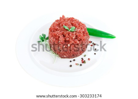 very big raw hamburger cutlet with sprouts and chilli pepper on white plate isolated over white background - stock photo