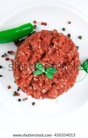 very big raw hamburger cutlet with sprouts and chilli pepper on white plate isolated over white background