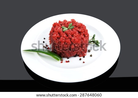 very big raw hamburger cutlet with sprouts and chilli pepper on white plate over black background - stock photo