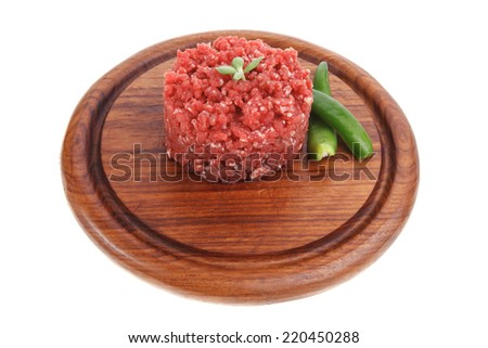very big raw hamburger cutlet with sprouts and chilli pepper on wooden plate isolated over white background - stock photo
