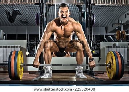 very brawny guy bodybuilder ,  execute exercise deadlift with weight, in gym - stock photo