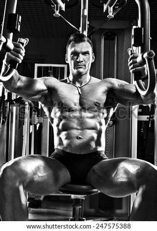 very brawny guy bodybuilder ,  execute exercise  on gym apparatus Butterfly Machine, in gym. Black-and-white photo - stock photo