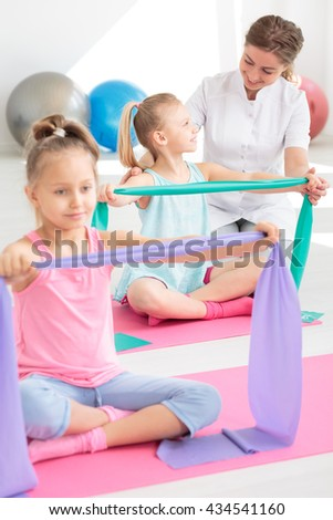 Very bright exercise room with two school girls exercising with resistance bands on pink mats - stock photo