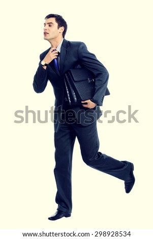 Very busy businessman with briefcase running to important meeting - stock photo
