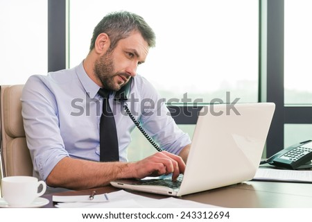 Very busy. Confident mature man in shirt and tie working at laptop and talking on the phone while sitting at his working place